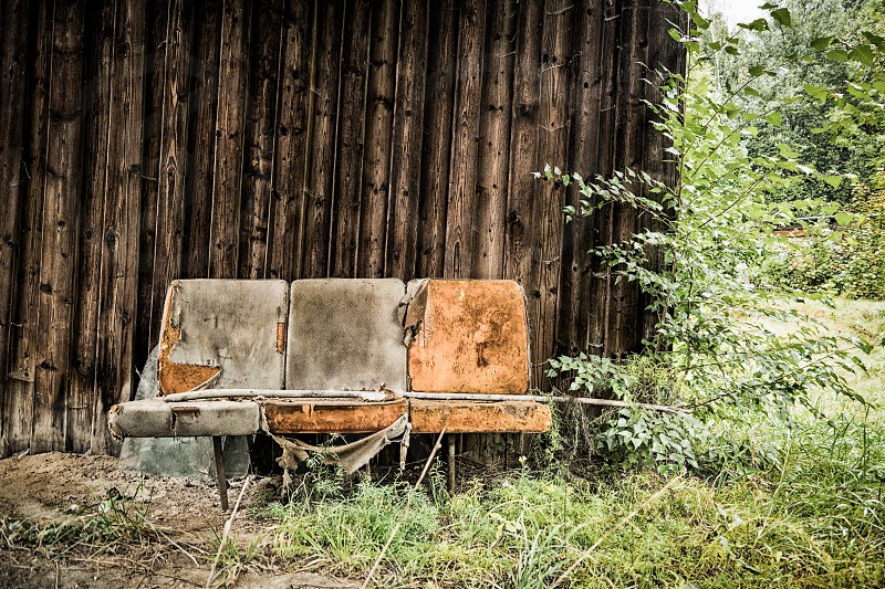 Seats sit upholstered natural wall wood wooden wall lawn shrubs old rustic dilapidated broken worn weathered torn leather wood lath brown orange photo