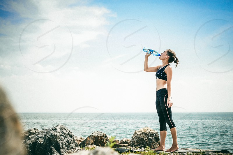 athletic woman drinking water from a bottle on the beach on a warm summer day exercise in open air photo