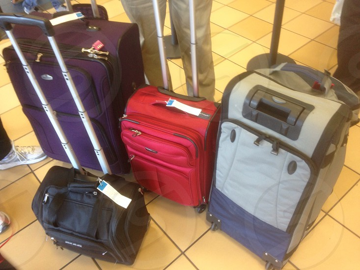 red purple black and grey travelling bag on top of brown tiles photo