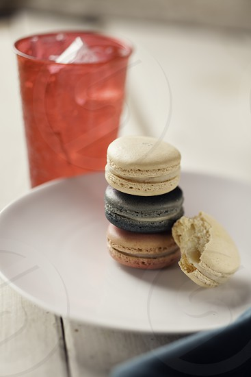 Red white and blue macaroons on a small plate on a table made of whitewashed wood. photo