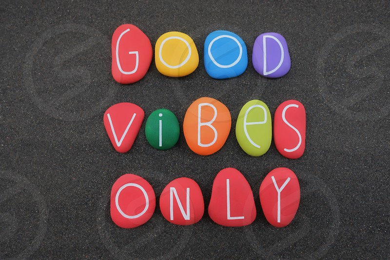 Good Vibes Only positive phrase for a better life composed with multi colored stone letters over black volcanic sand photo