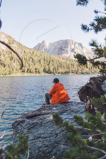 man wearing orange bubble jacket sitting on rock near river photo
