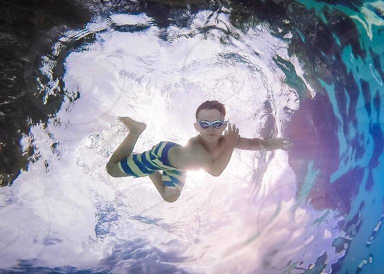 Boy swimming underwater sun photo