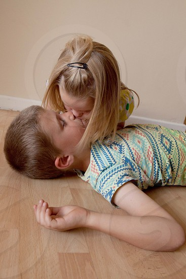 boy lying with girl giving him restitution photo