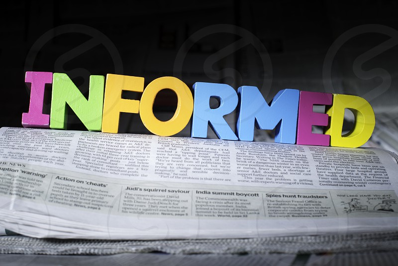 Word informed on newspaper. Wooden letters photo