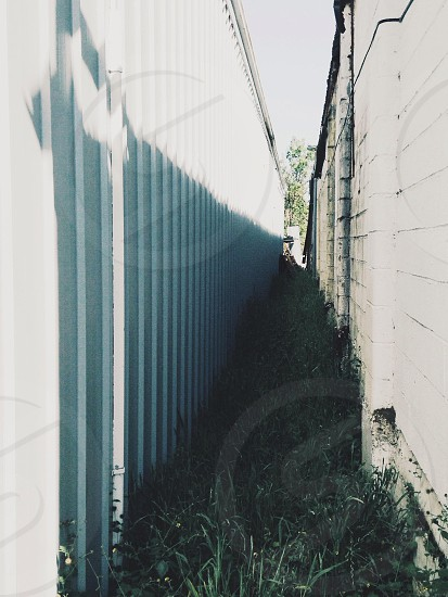 narrow grass road between metal sheet and concrete wall photo
