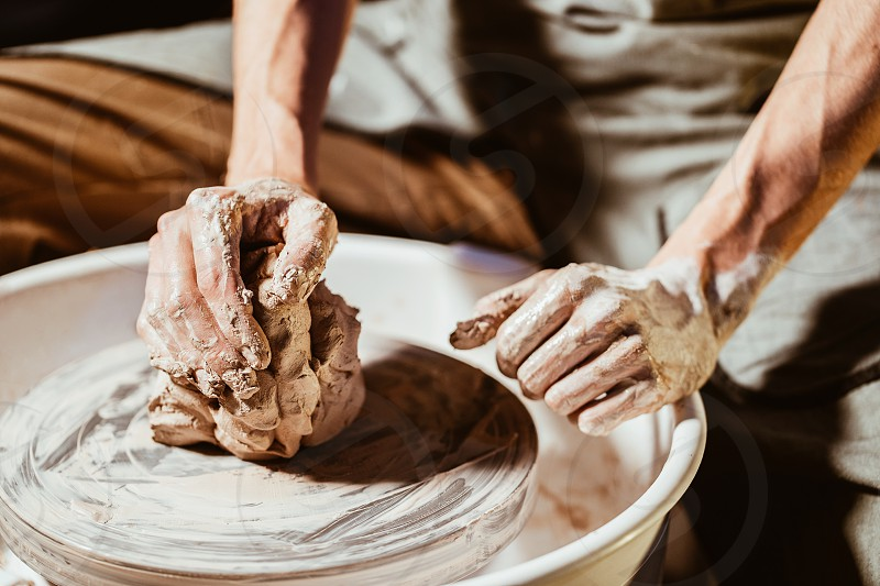 Artisan potter prepares material clay for pottery. Man knead clay before molding. Male sculptor is pugging and kneading clay for creating ceramics in his studio. photo