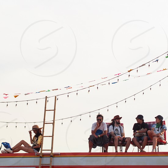 Chilling on the roof of a camper van at a festival. photo