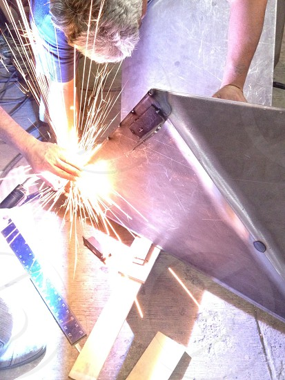 person welding a metal photo