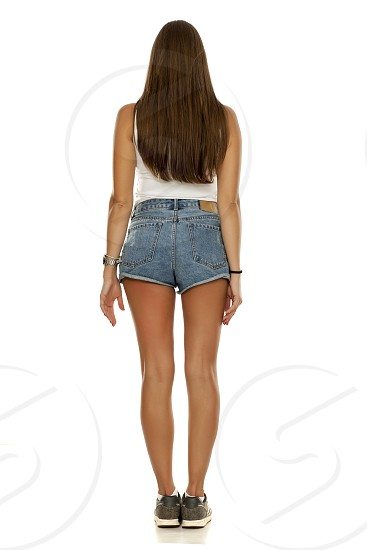 Back view of a young beautiful woman in shirt short jeans and sneakers posing on white photo