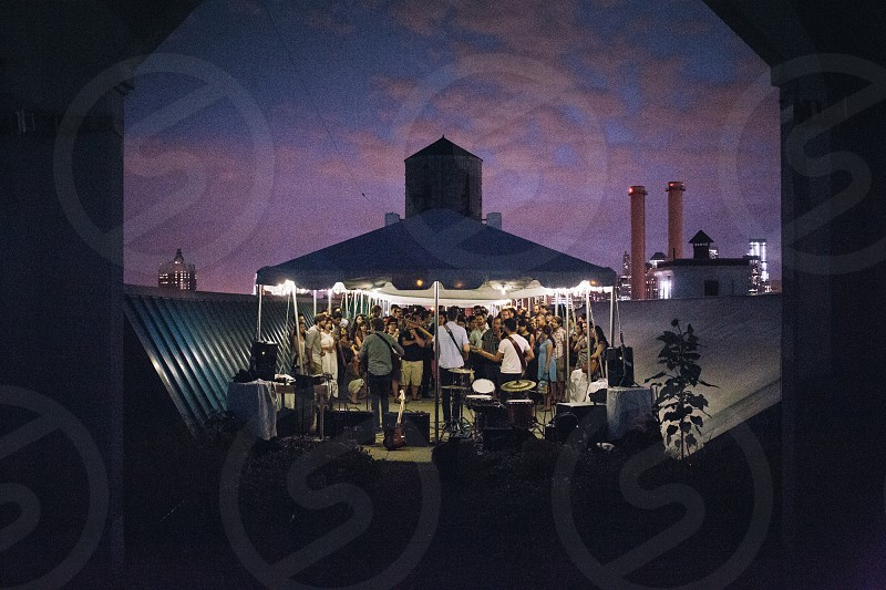 band performing in front of crowd in rooftop gazebo during dusk photo
