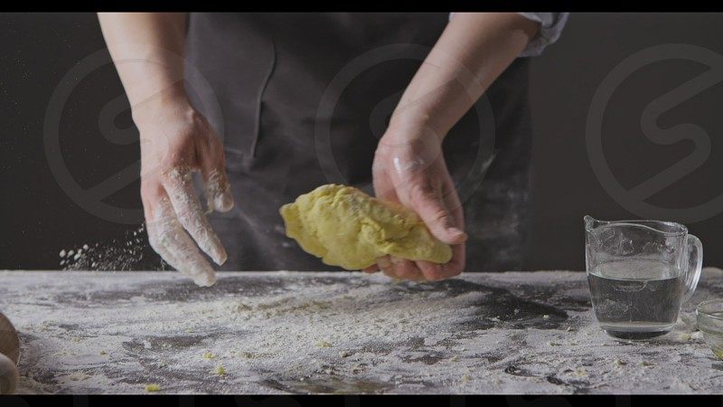 Process of preparation homemade dough. Chef woman's hands knead natural products for pasta on a kitchen table step by step. Slow motion Full HD video 240fps 1080p. photo