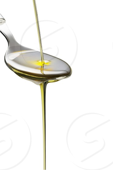 olive oil poured on a spoon over white background photo
