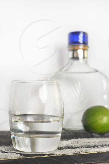 clear rocks glass beside clear glass bottle and lime fruit photo