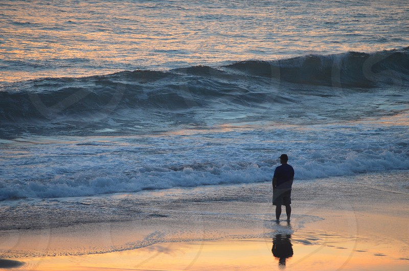 Man looking at waves and ocean sunset calm quiet photo