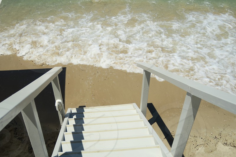 Wooden staircase to a Mediterranean beach. Wooden stairs walkway leading to a sandy beach on a summer day. photo