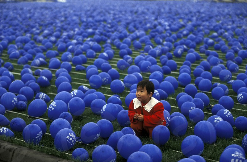 a chila in blue ballons on a economy fair in the city Square of Chengdu in the provinz Sichuan in centrall China. photo