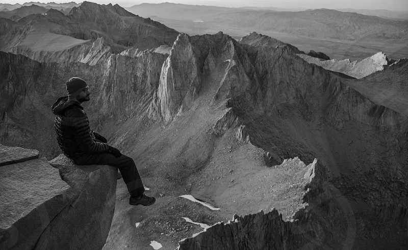black and white photo of man sitting on cliff photo