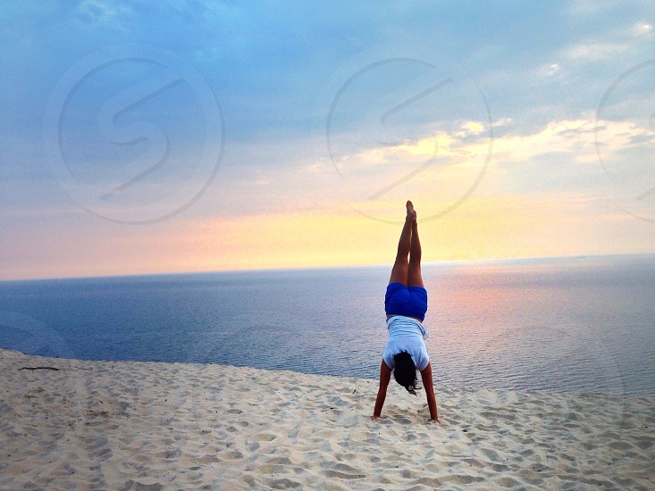 Handstands and having fun on the beach sand dunes at sunset.  photo