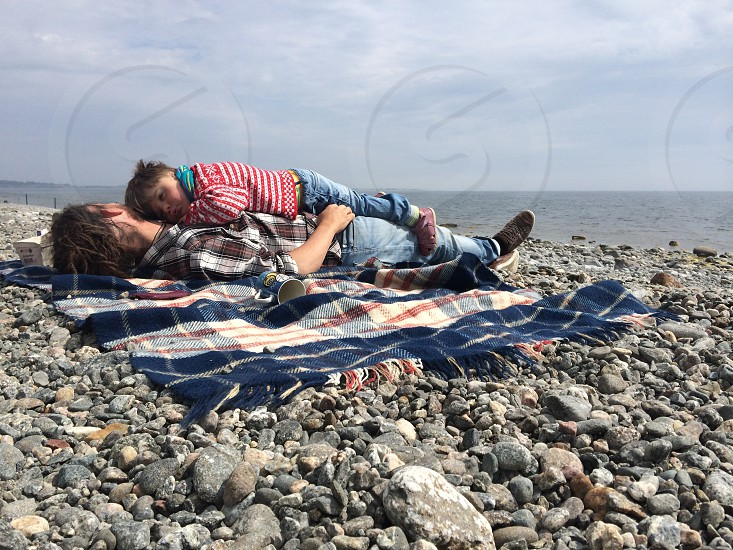 rocky beach with white blue and red plaid blanket photo