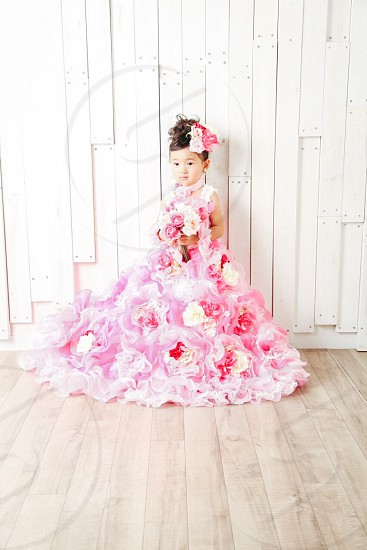 girl wearing pink red and white floral sleeveless ruffle ballgown holding bouquet standing behind white wooden wall photo