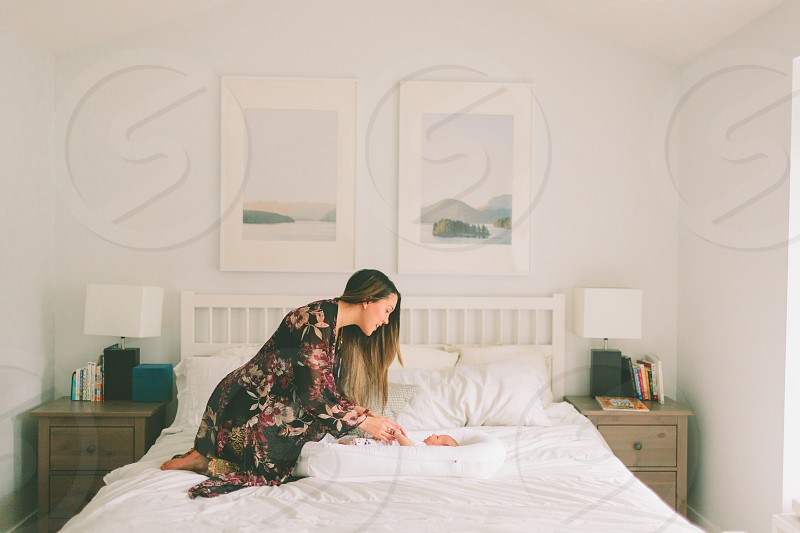 A mother and baby in a clean simple bedroom.  photo