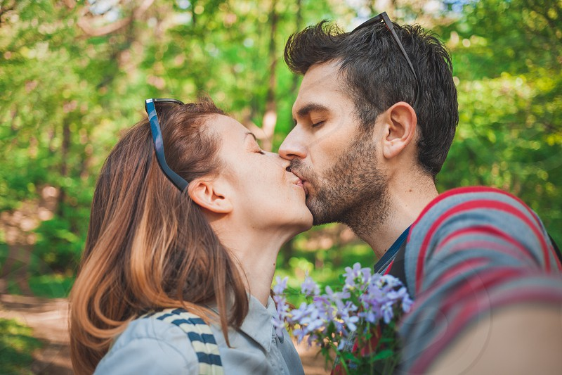 Young couple in love taking a selfie while kissing in the park photo