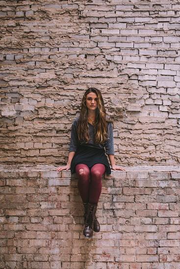 woman in blue elbow shirt sitting on brown concrete bricks photo