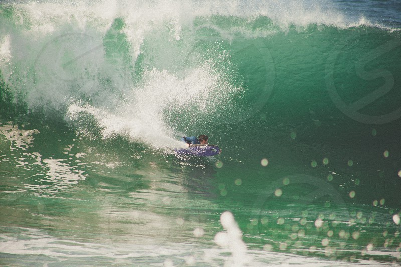 man surfing on sea waves during daytime photo