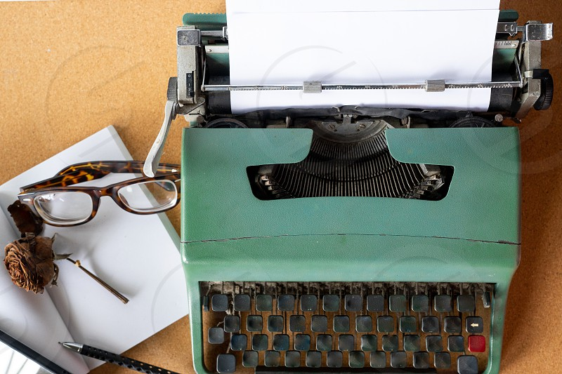 Vintage old mint green typewriter with plain white  paper on cork wooden board with pens and witered rose retro glasses and blank book on side. photo