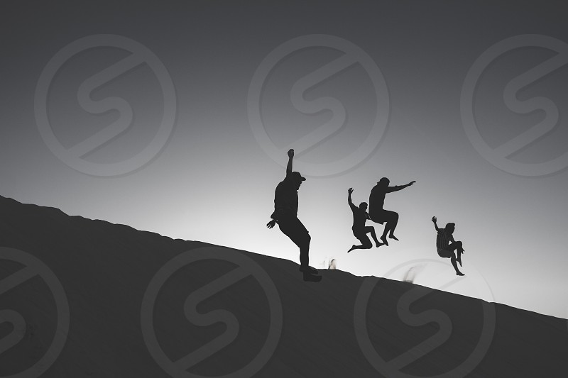 grayscale photo of four people jumped from sand photo