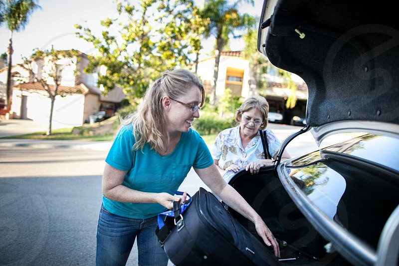 A young woman in a turquoise T-shirt and jeans helps a lady load a suitcase into the open trunk of a silver sedan on a suburban neighborhood curbside. photo