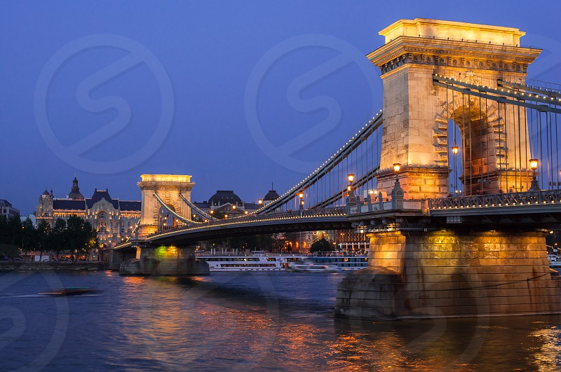 Europe Budapest chain bridge travel blue night Danube river boats photo