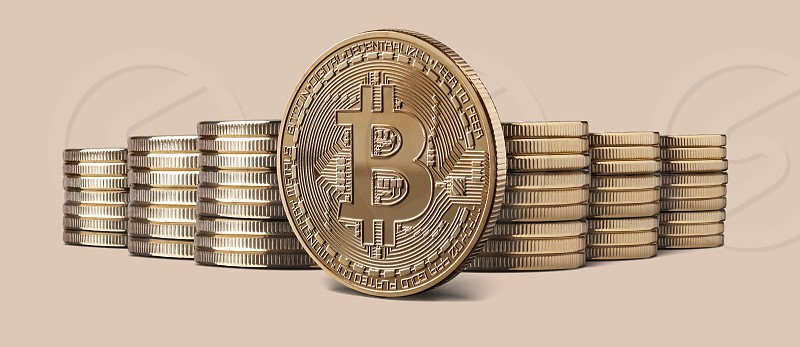 Cryptocurrency physical gold bitcoin coin and Stacks of bitcoins standing against a beige background. Cryptocurrency and blockchain trading concept. Can be used for video or site cover photo