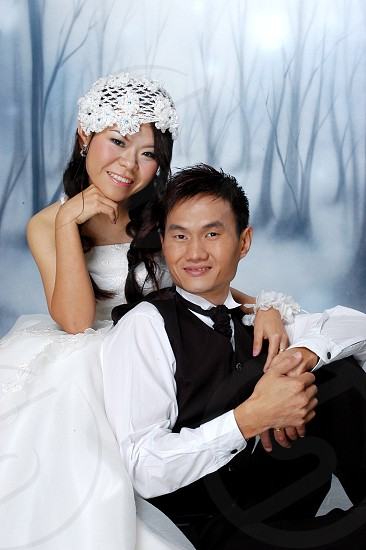 man in black vest and white dress shirt sitting beside woman in white wedding gown photo