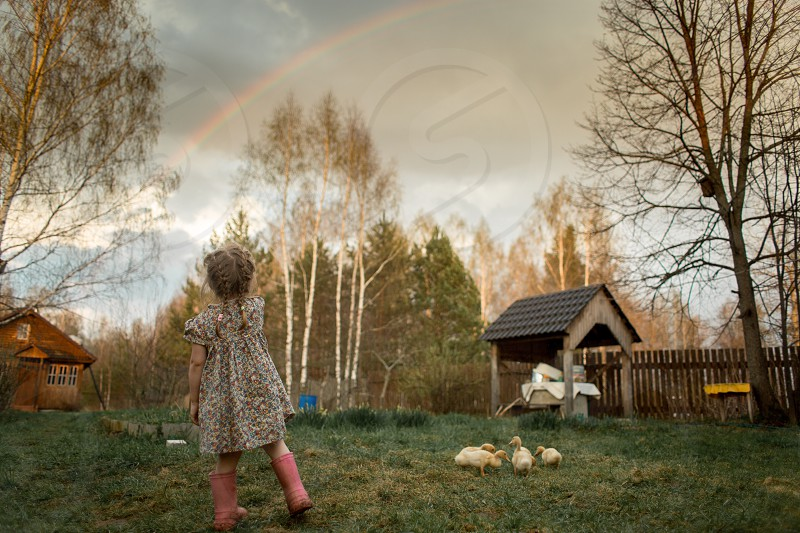 Portrait of a little girl looking on the rainbow  in an spring courtyard  photo