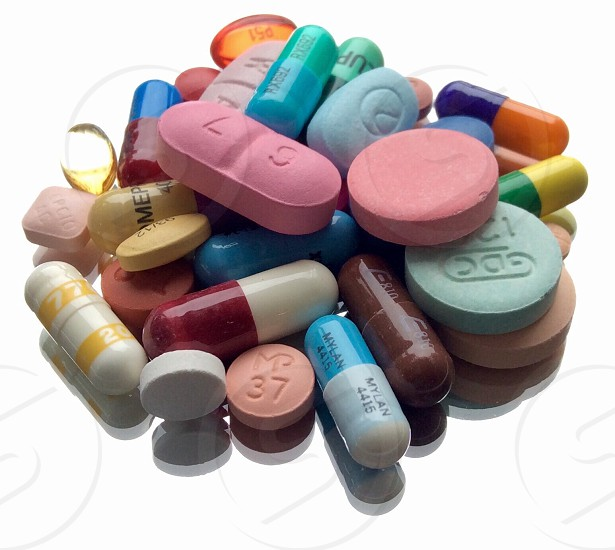 medication pills capsule and caplets on white surface photo