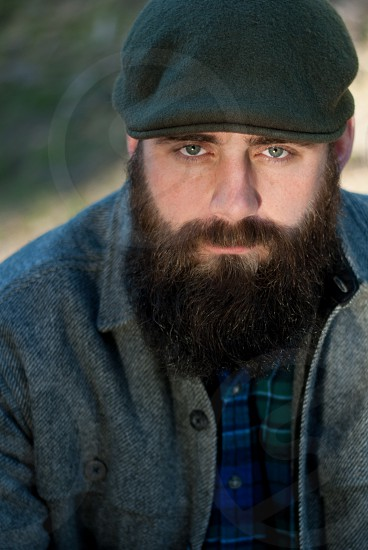 Bearded man sitting in outdoors with cap on and serious look photo