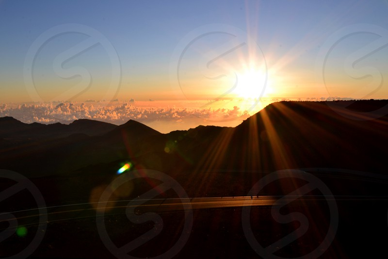 sunrise above white clouds and mountain photo