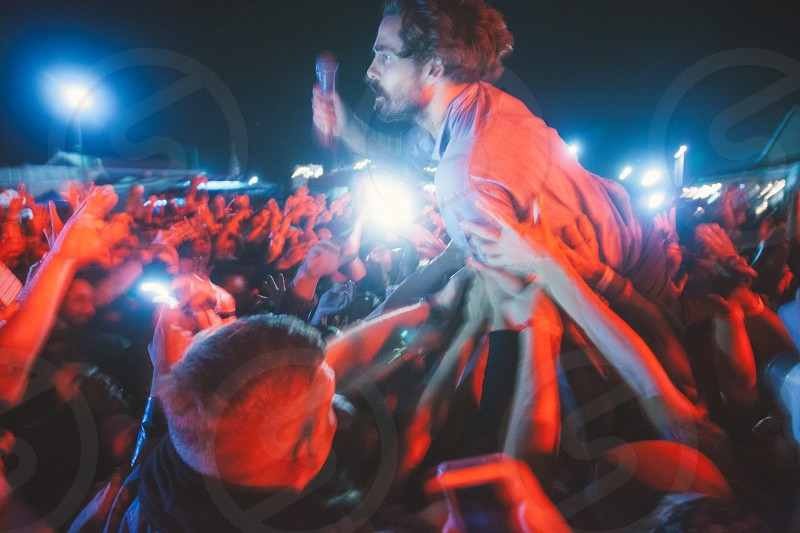 man with a microphone crowd surfing at a concert photo