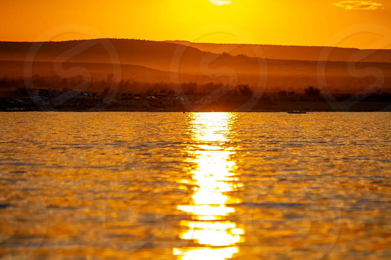 The reflection of sunlight streams on the golden sunset water of Lake Powell in Wahweap Bay.  The focal point is somewhere mid image and the rest is soft focus.  Great background image with copy space. photo
