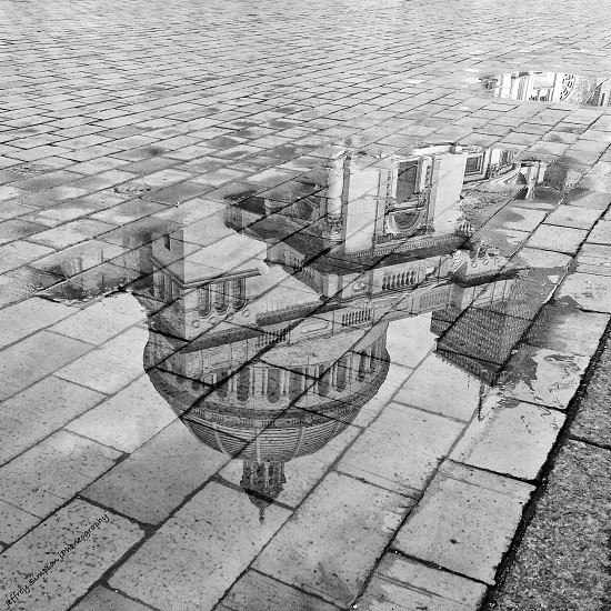 reflection of a building in a puddle photo
