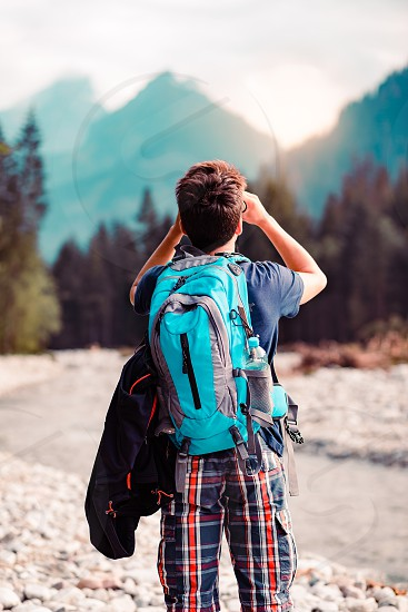 Young wanderer with backpack looks through a binoculars on mountains peaks stands over a river. Boy spends a vacation in mountains wandering with backpack he is wearing sports summer clothes photo