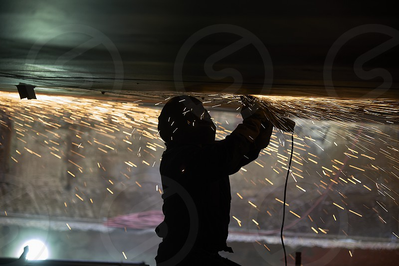 Silhouette of a welder hard at work at a shipyard underneath a large vessel with fire sparks flying around everywhere photo