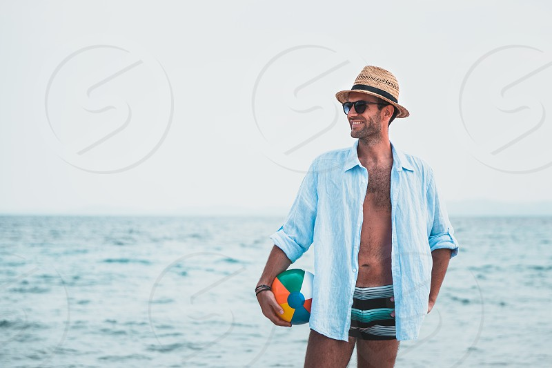 Young man holding ball at the beach photo