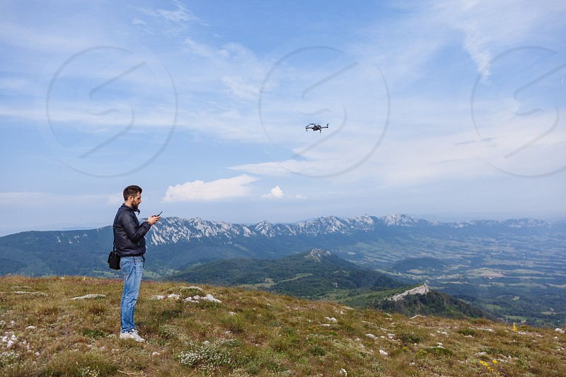 Young man flying drone on mountain photo