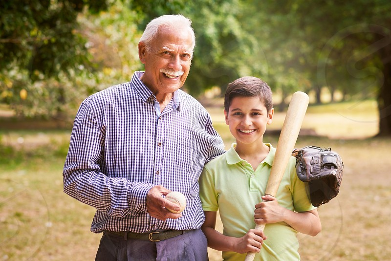 baseball bat portrait family playing senior boy grandpa grandfather looking at camera embracing smile smiling two people active activity age difference ball cheerful child elderly exercise generation gap glove grandchild grandparent grandson happy healthy hispanic holding hug hugging kid latin american leisure lifestyle man old outdoor park people recreation retired retiree retirement sport together young photo