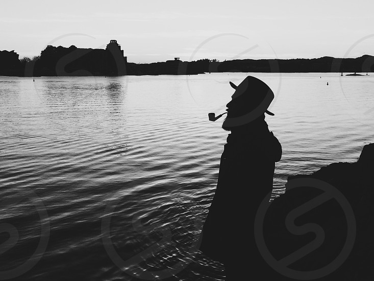 man with smoking pipe in mouth standing near body of water black and white photo photo