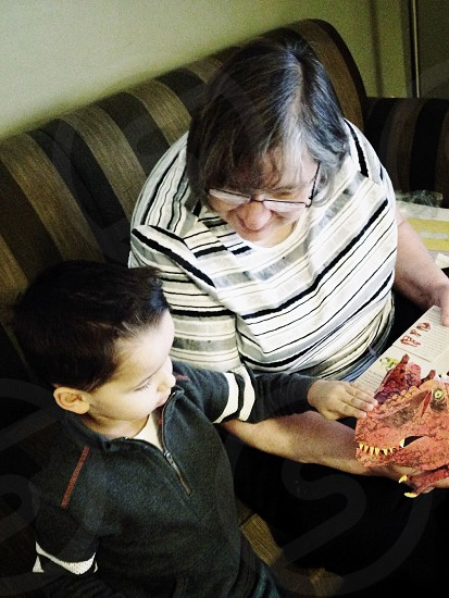 woman teaching boy  about dinosaurs while sitting on couch photo