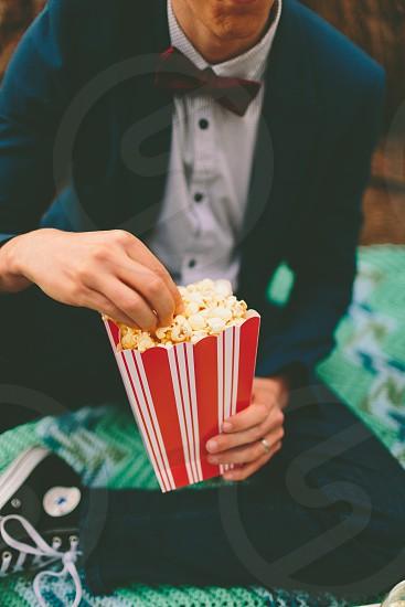 A man eating popcorn.  photo